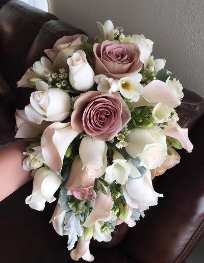 Bridal bouquet made from soft pink and cream roses and white fresia