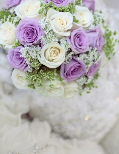Brides wedding bouquet of cream and light purple roses surrounded by babies breath