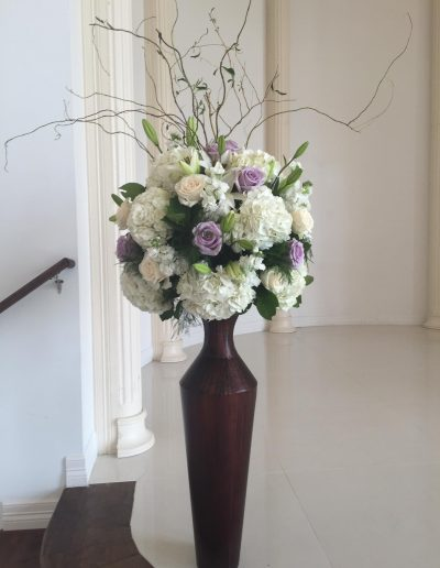 Ceremony vase filled with Cream and like purple roses and white carnations