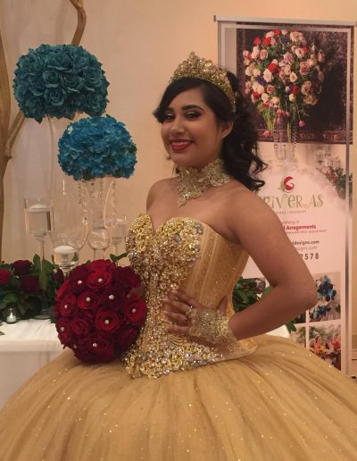 Golden Quinceañeras dress with Red bouquet and diamond studded centers