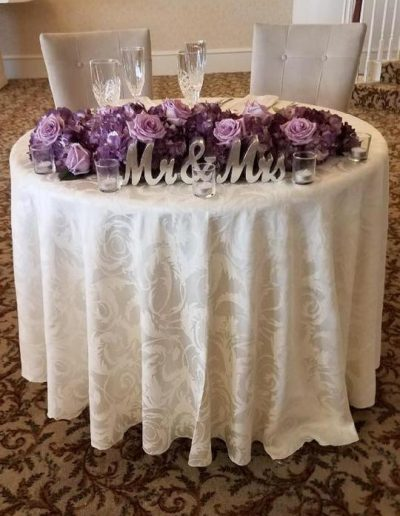 Mr. and Mrs. Sweet heart table covered in purple Garden roses