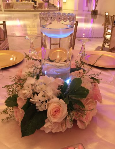 Pink and wihte flowers with candle in water of vase