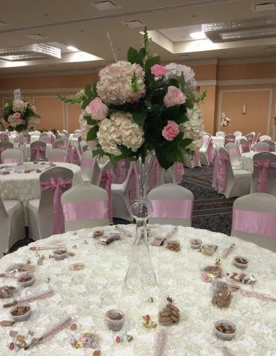 Pink roses and carnations with large cream carnation and greenery for tables