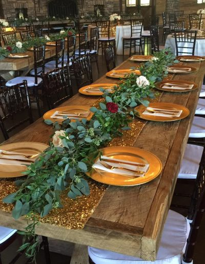 Reception tables with greenery end to end with red and white roses