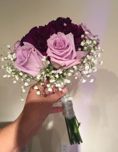 Small wedding bridal bouquet of light purple flowers and Burgundy carnations