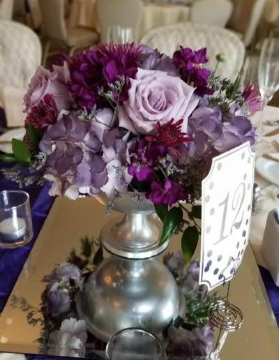 Vibrant purple centerpiece wedding reception purple roses and purple carnations