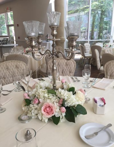 Wedding Reception table centerpiece of candles with white hydrangeas and pink rose base
