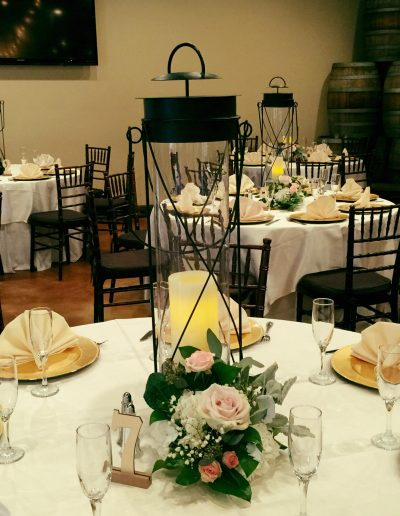 Wedding centerpiece candles surrounded by white roses and greenery