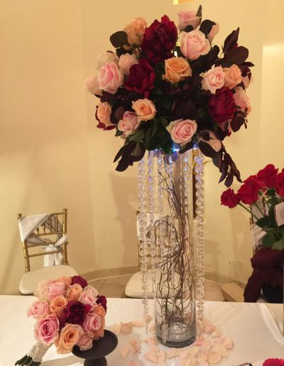 Wedding reception centerpiece with lights filled with pink, peach and red roses with greenery