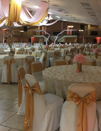 wedding reception filled with pink roses and tables covered with white and gold